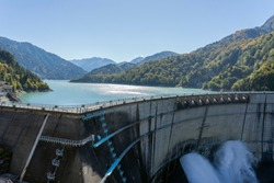 Water Turbines Are Producing Electricity At Power Plant. Panorama View Of Hydro Power Station And People On The Kurobe Lake Dam,Toyama. River Dam and Tateyama Mountains.