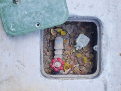 Water valve box in outdoor cement floor Inside there is an open-close water valve for use in a sprinkler system in the lawn or garden. On a cement background.