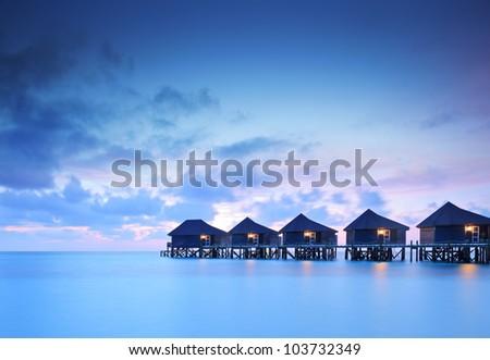 Water villa cottages at sunset on island of Kuredu, Maldives, Lhaviyani atoll