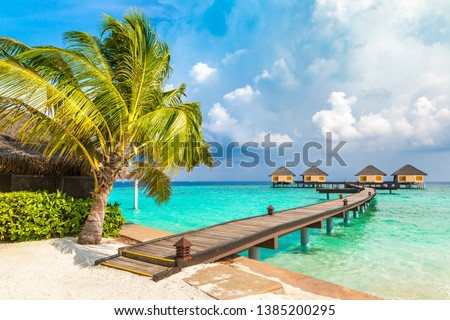 Water Villas (Bungalows) and wooden bridge at Tropical beach in the Maldives at summer day #1385200295