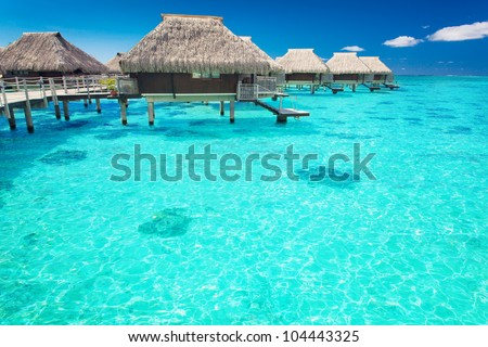 Water villas in the ocean with steps into turquoise lagoon