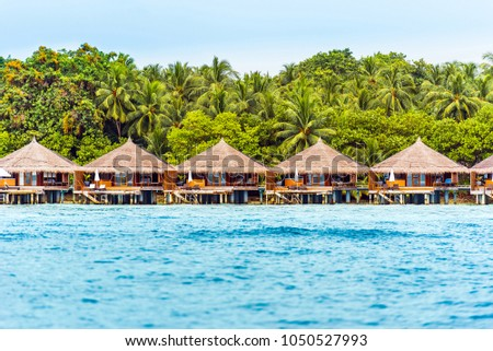 Water villas on tropical caribbean island, Maldives. Copy space for text.                              #1050527993