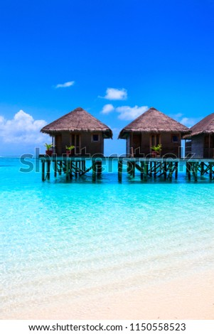 Water villas on wooden pier in turquoise ocean on the white sand beach #1150558523