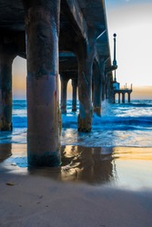 Water waves crash into concrete pillars under beach pier as the sun sets in background. Empty scenic outdoor location on a relaxing evening.