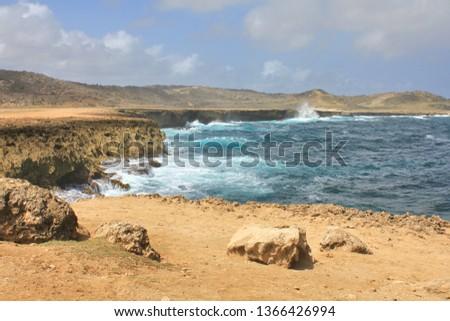 Water waves crashing on the cliffs of Aruba island. Netherland Antilles on Caribbean sea. Сток-фото ©