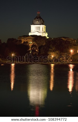 Water with reflection of South Dakota State Capitol and complex at night, Pierre, South Dakota