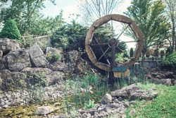 Water wooden old wheel mill in country village near pond stream. Retro vintage machinery in idyllic rustic rural country-side.