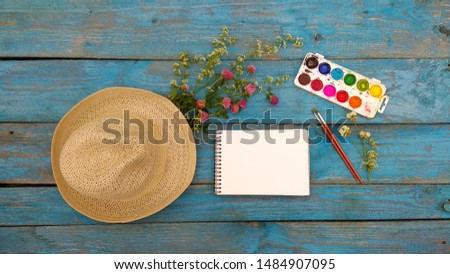 Watercolor, brushes, sketchbook, clover bouquet, men's hat on the table. Top view of art supplies for plein air. Flatlay for mockup, desktop, background, postcard, calendar.