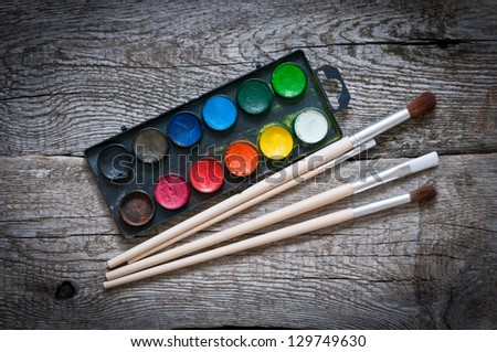 Watercolor paint and brushes on wooden background