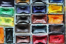 Watercolor paint pans of diverse colors, red, yellow, blue, brown and others, as a creative arts hobby or career and symbol of diversity.