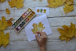 Watercolor paints on a wooden table with a pattern on white paper and a brush. Artist's workplace. Mockup for elegant design.