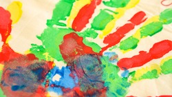 Watercolor paints. Traces of paint from the hands and fingers of children. Beautiful drawings of flowers. Art therapy. Hobby. Artists. Silhouettes of hands. Blue and green. Children's drawings. School