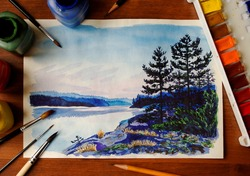 watercolor picture of lake, surrounded with brushes and paints
