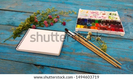 Watercolor, sketchbook, brush, bouquet lie on the table. Top view on art accessories for an open air. Flatlay for mockup, desktop, background, postcard, calendar in the style of provence.