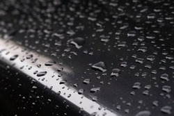 Waterdrops on a darkgray metallic car. Focus on the large drop in front