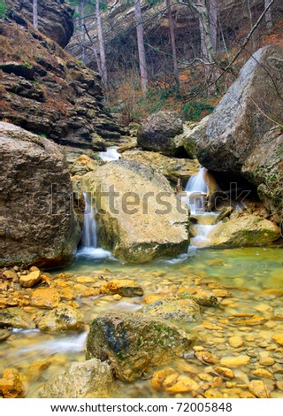Waterfall amongst greater stone in wood. Natural composition