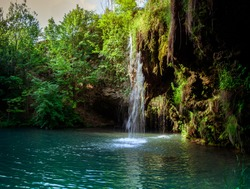Waterfall and a beautiful lagoon lake for relaxing in the summer forest