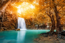Waterfall and blue emerald water in autumn forest with sun flare and sunlight in morning. Erawan Waterfall step 3rd. Beautiful nature rock waterfall steps in rainforest at Kanchanaburi, Thailand