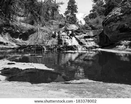 Waterfall and mountain rock in forest, monotone black and white color