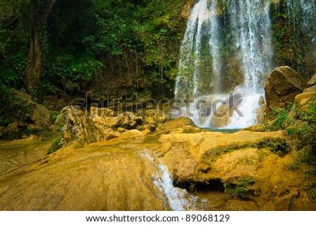 Waterfall and river flowing among rocks in the cuban natural landmark of Soroa