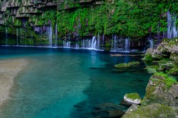 Waterfall and upstream river landscape in the deep forest with green moss in Kagoshima, Japan