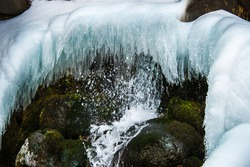 Waterfall basin with icicles in the middle of winter