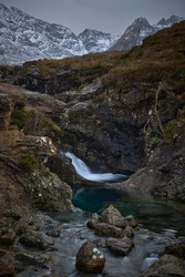 waterfall between giant stones and snow mountains. loose stones in the foreground and turquoise water - Fairy Pools - Skye Island - Scotland - Uk