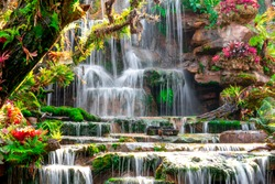 Waterfall concept, motion waterfall on stone in beautiful nature on hills, many level slope flowing, splash and stream beauty clean fresh in forest, popular for travel of tourist in Thailand