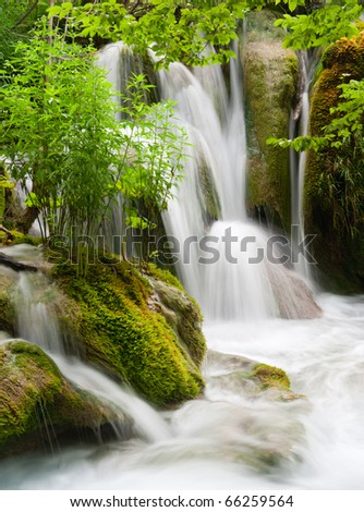 Waterfall currents in national park. Plitvice, Croatia. Popular touristic destination with lush vegetation.