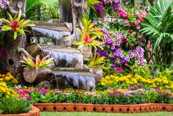 Waterfall flows and vivid flowers pot decoration in cozy home flower garden on summer.