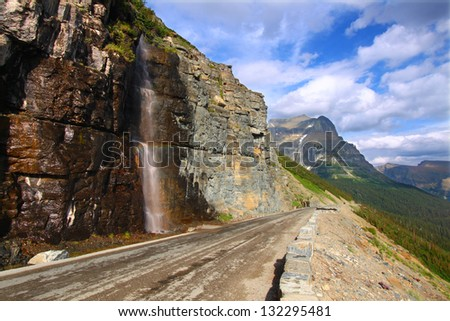 Waterfall flows down from the mountains onto the Going To The Sun Road in Glacier National Park - Montana.