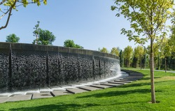 Waterfall flows in streams into granite bed of artificial river. Fountain in form of huge bowl. Public landscape city park Krasnodar or 'Galitsky park' for relaxation and walking in sunny autumn 2020