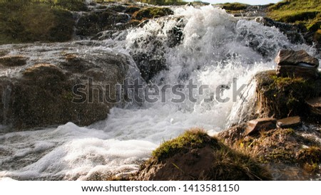 Waterfall formed with snow water in the mountains
