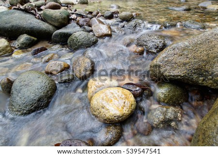 waterfall in blurring with a flowing waters. Stones are around the waters #539547541