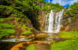 Waterfall in green forest mountains