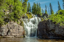 Waterfall in northern Sweden with water falling in stages or steps down a steep mountain side. Long exposure with soft and smooth water, green trees and blue sky