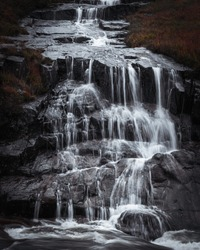 Waterfall in Scottish Highlands, in Etive valley, Glencoe, Scotland,UK.Power in nature.Flowing water.Cascade and dark rocks.Nature image with atmospheric mood.Tranquil landscape scene.