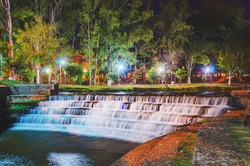 Waterfall in sequence of steps made by man on a long exposure photo. Water with smooth movement, nature around and city lights. Waterfalls on the lake Lago Igapo in Londrina city, Brazil.
