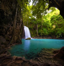 Waterfall in tropical forest. Beautiful nature background. Jungle trees and blue water of mountain river in national park in Thailand, Asia.