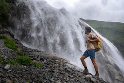 Waterfall Landscape and male Traveler enjoying waterfall view. active vacations into the wild harmony with nature. Image for hiking or climbing. Alibek Waterfall, North Caucasus, Dombai, Russia.