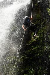 waterfall man climb spelunking rock rain forest descending male descending a huge waterfall in ecuadorian rainforest waterfall man climb spelunking rock rain forest descending journey sport canyon wat