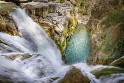 waterfall of a mountain river seen from above, the water falls into a pool of crystalline waters in the Anisclo Canyon, in the Pyrenees of Huesca, Spain