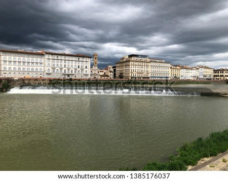 Waterfall of Arno river, Florence, Italy before rainfall in angry mood.