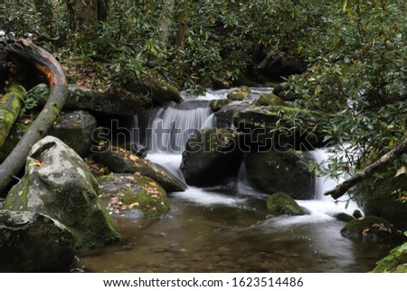 Waterfall on a small stream with green moss growing all around it.