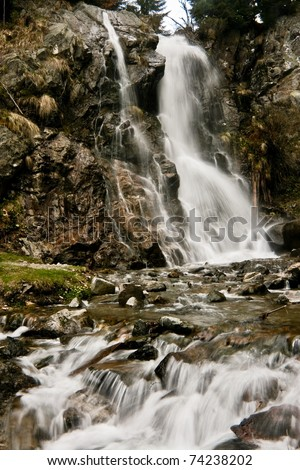 Waterfall over rocks with moss and lichens.  Beautiful place in the Carpathians during a rainy spring day