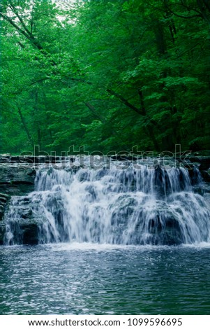 Waterfall surrounded by lush greenery #1099596695