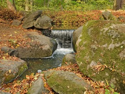 Waterfall surrounded by mossy stones and fallen leaves in Sofiyivsky or Sofiyivka Arboretum Park, Uman City, Ukraine, in autumn