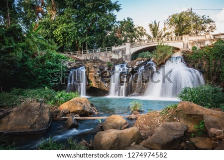 Waterfall under Bridge with long exposure silky effect scenic and creative with green trees