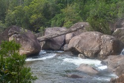 Waterfall with a strong flood of water rocks below.Crystal clear water, huge stones with a beautiful vegetation around. At the end forming a strong current and later a calm lake with clean transparent