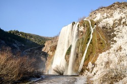 Waterfall with rainbow at sunset at cold winter day. Falling water of Krcic into the source of the Krka River. 22 meter high waterfall. Topoljski slap, Krka, Knin, Croatia. Ice and snow.